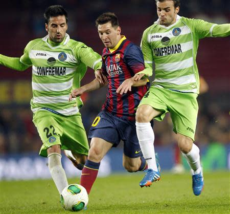 Barcelona's Messi fights for the ball against Getafe's Rodriguez and Leon during their Spanish King's Cup match at Camp Nou stadium in Barcelona
