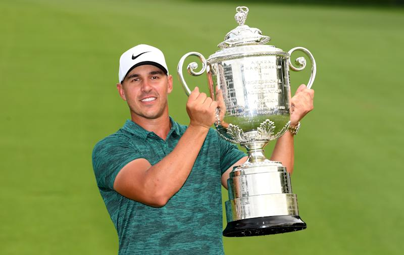 Brooks Koepka celebrates with the winners trophy on the 18th green after winning the 2018 PGA Championship at Bellerive Golf & Country Club on August 12, 2018 in St Louis, Missouri.