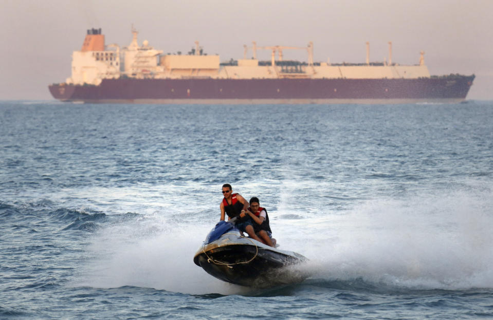 FILE - In this Friday, July 26, 2019 file photo, a ship crosses the Gulf of Suez towards the Red Sea as holiday-makers ride a jet ski at al Sokhna beach in Suez, 127 kilometers (79 miles) east of Cairo, Egypt. Not only are humans changing the surface and temperature of the planet, but also its sounds – and those shifts are detectable even in the open ocean, according to research published Thursday, Feb. 4, 2021. (AP Photo/Amr Nabil)
