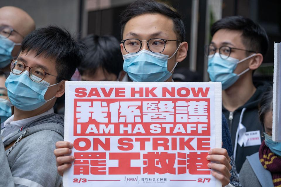 A masked medical staff holds a placard during the strike outside the Hospital Authority building in Hong Kong. Source: Getty