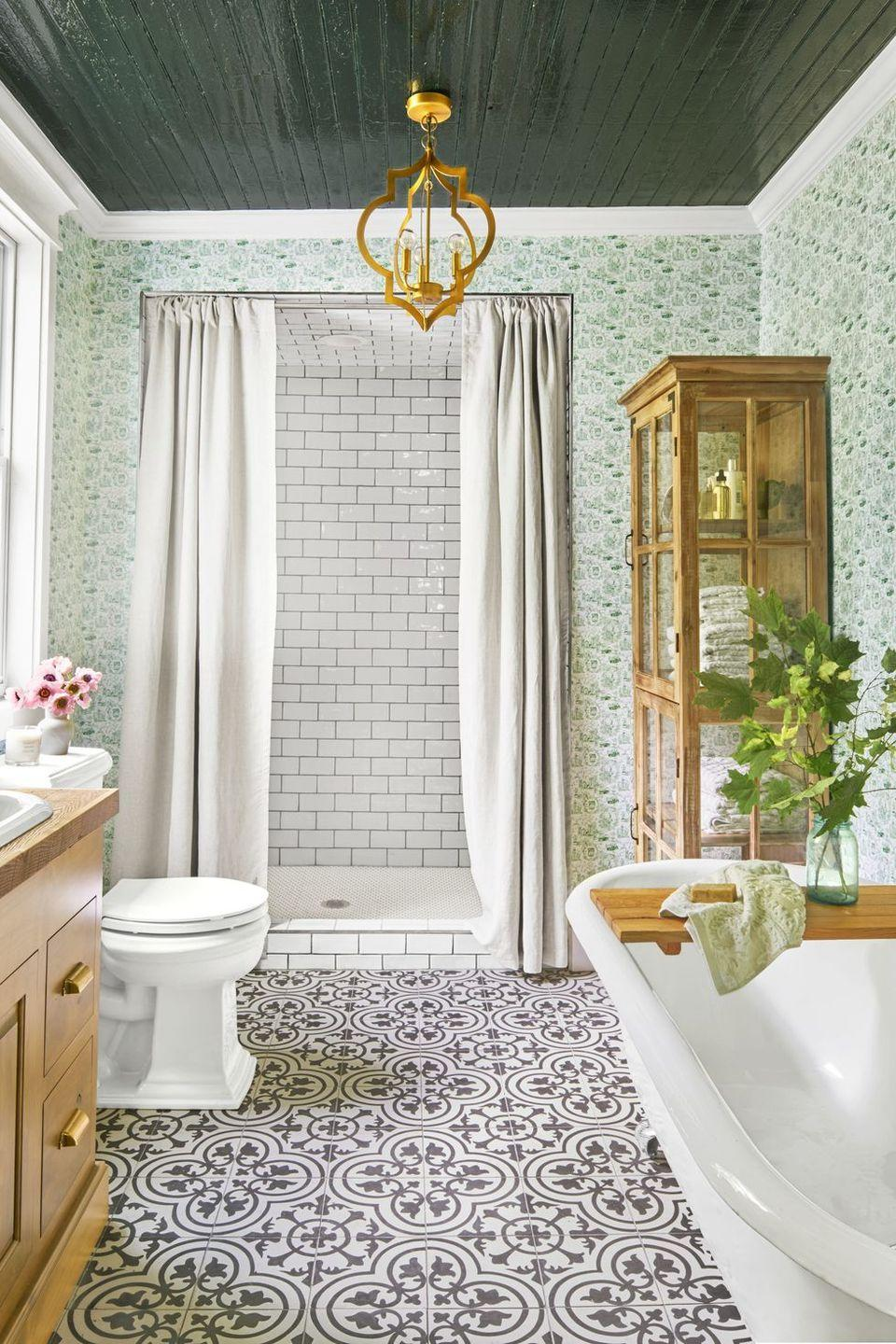 <p>A mix of patterned and subway tiles balance this bathroom's wallpapered walls and dark ceiling. </p>