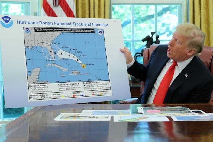 In the Oval Office of the White House, President Donald Trump holds a chart showing the original projected track of Hurricane Dorian that appears to have been extended with a black line to include parts of the Florida panhandle and Alabama on Sept. 4, 2019. (Photo: Jonathan Ernst / Reuters)