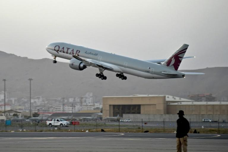 A Qatari security personnel stands guard as a Qatar Airways aircraft takes off from the airport in Kabul on September 9, 2021 (AFP/WAKIL KOHSAR)