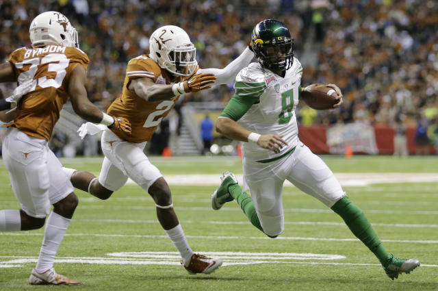 Oregon's Marcus Mariota (8) is chased by Texas' Mykkele Thompson (2) during the first quarter in the Valero Alamo Bowl NCAA college football game, Monday, Dec. 30, 2013, in San Antonio. (AP Photo/Eric Gay)