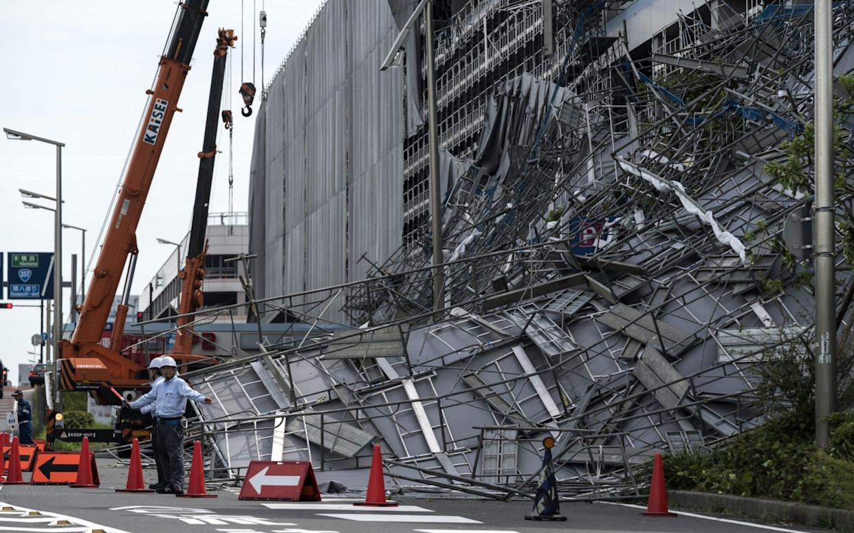 Workers direct traffic in front of damaged scaffolding at the construction site of a parking garage at Haneda Airport - Getty Images AsiaPac