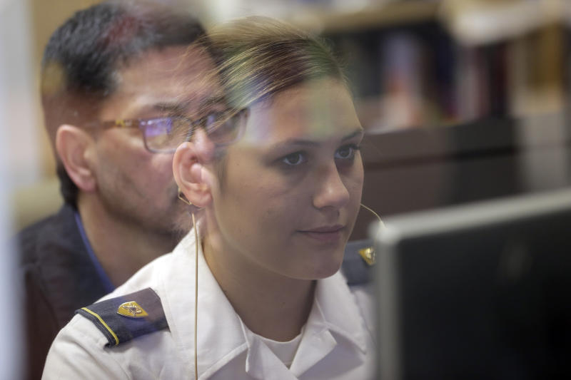 """In this file photo from May 2, 2019, visiting scientist Richard DiNinni, reflected in glass, watches as Cadet Cheyenne Quilter works with a virtual reality character named """"Ellie"""" at the U.S. Military Academy at West Point, N.Y. Artificial intelligence is spreading into health care, often as software or a computer program capable of learning from large amounts of data and making predictions to guide care or help patients. (AP Photo/Seth Wenig, File)"""