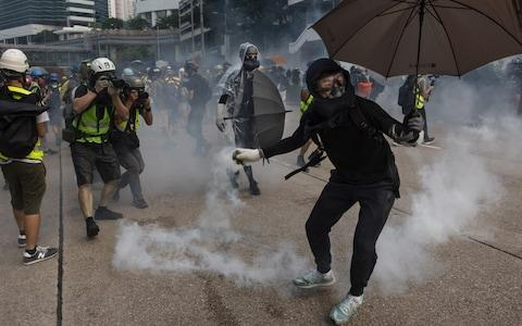 A Hong Kong protester throws back a tear gas canister at the police - Credit: Andolu Agency via Getty