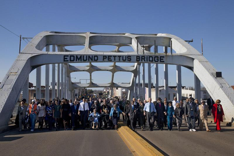 "FILE - In this Saturday, March 7, 2015 file photo, President Barack Obama, first lady Michelle Obama, their daughters Malia and Sasha, as well as members of Congress, former President George W. Bush, and civil rights leaders make a symbolic walk across the Edmund Pettus Bridge in Selma, Ala., on the 50th anniversary of ""Bloody Sunday,"" a civil rights march in which protestors were beaten, trampled and tear-gassed by police at the site. The incident led to the passage of the Voting Rights Act in 1965. (AP Photo/Jacquelyn Martin)"