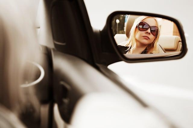 young woman looking in the car...