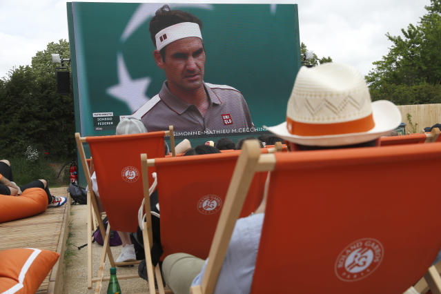 Spectators in lounge chairs watch Roger Federer, on screen, rear, play Italy's Lorenzo Sonego during their first round match of the French Open tennis tournament at the Roland Garros stadium in Paris, Sunday, May 26, 2019. (AP Photo/Pavel Golovkin)