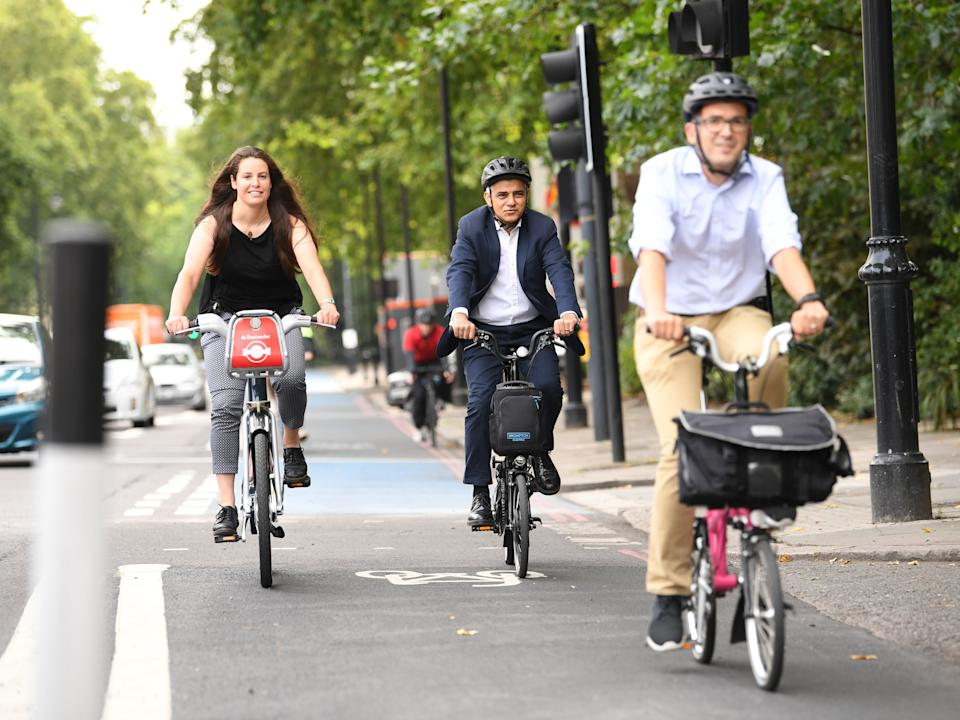 Mayor of London Sadiq Khan (centre) tries out a protected cycle lane alongside Will NormanPA