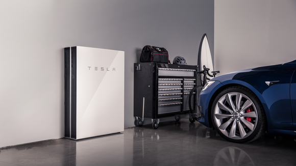 A Tesla Powerwall 2 in a garage, next to a Tesla vehicle