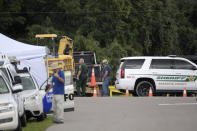"""A Sarasota County Sheriff's Office deputy and a Sarasota County worker direct a truck carrying excavating equipment into the Carlton Reserve during a search for Brian Laundrie, Tuesday, Sept. 21, 2021, in Venice, Fla. Laundrie is a person of interest in the disappearance of his girlfriend, Gabrielle """"Gabby"""" Petito. (AP Photo/Phelan M. Ebenhack)"""