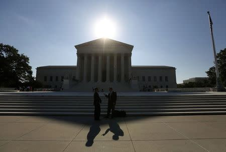 Two men talk as the sun rises over the Supreme Court in Washington