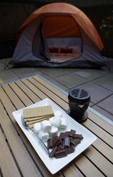 "Along with a tent on your patio, smores are an option at the Affina Hotel in New York, Thursday, Aug. 15, 2013. A couple of New York City locales are offering an unusual option _ the chance to sleep outdoors, incredibly comfortably. It's an urban take on ""glamping,"" where hotel comforts are taken outside. (AP Photo/Seth Wenig)"
