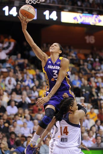 Los Angeles Sparks' Candace Parker, left, drives past Connecticut Sun's Tan White during the first half of a WNBA basketball game in Uncasville, Conn., Wednesday, June 13, 2012. (AP Photo/Fred Beckham)