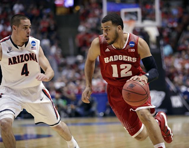 Wisconsin 's Traevon Jackson drives past Arizona's T.J. McConnell during the first half in a regional final NCAA college basketball tournament game, Saturday, March 29, 2014, in Anaheim, Calif. (AP Photo/Jae C. Hong)