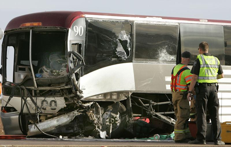 Emergency personnel survey the damage to a tour bus that was struck by a pickup truck traveling east in the the westbound lanes of Interstate, Tuesday, Nov. 20, 2012 in Casa Grande, Ariz. The driver of the truck was killed, two people were flown to Phoenix hospitals and six were transported to Casa Grande Regional Medical Center. The collision is under investigation by Arizona Department of Public Safety Highway Patrol. (AP Photo/Casa Grande Dispatch, Oscar Perez)