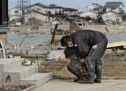 A man comforts a woman in front of her damaged home in Miyagi prefecture on March 14, 2011