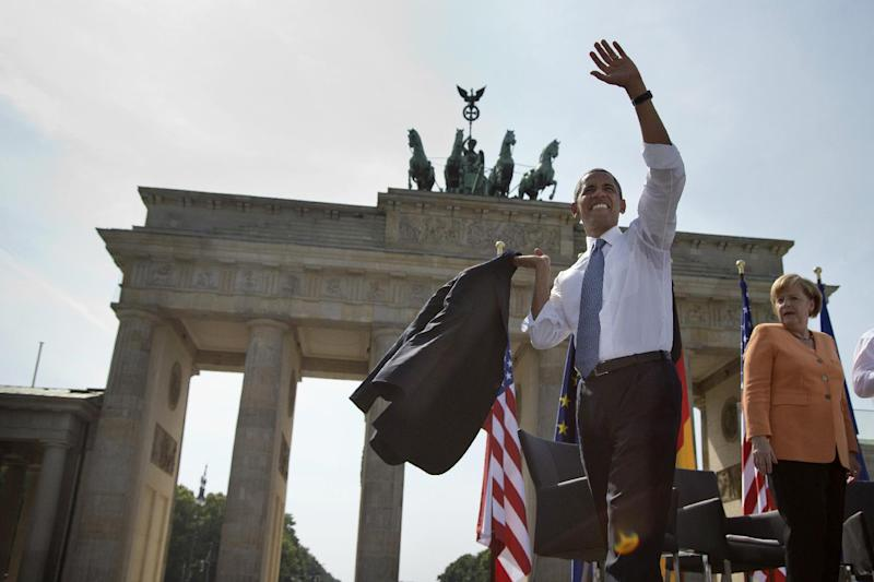 President Barack Obama, accompanied by German Chancellor Angela Merkel, waves before throwing his jacket over his shoulder as he arrives to speak at the Brandenburg Gate in Berlin, Wednesday, June 19, 2013. Obama called to reduce the world's nuclear stockpiles, including a proposed one-third reduction in U.S. and Russian arsenals, a senior administration official said. (AP Photo/Evan Vucci)