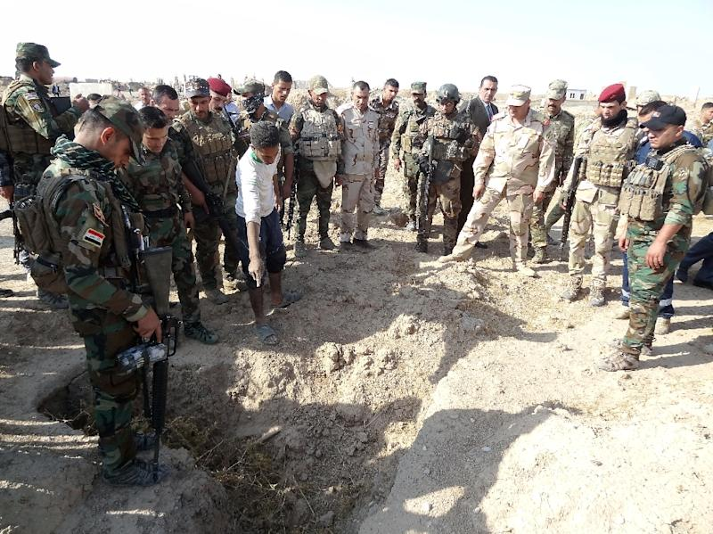 Iraqi forces search the site of a mass grave containing the remains of victims of the Islamic State group, near the the former jihadist bastion of Hawija on November 11, 2017