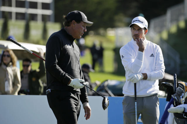 Phil Mickelson, left, and Nick Taylor, of Canada, talk while waiting to hit from the third tee of the Pebble Beach Golf Links during the final round of the AT&T Pebble Beach National Pro-Am golf tournament Sunday, Feb. 9, 2020, in Pebble Beach, Calif. (AP Photo/Eric Risberg)