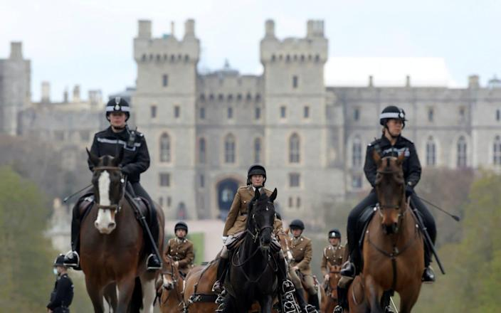 Members of The Kings Troop Royal Horse Artillery, flanked by police officers, ride their horses outside Windsor Castle - CARL RECINE