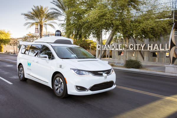 """A Waymo fully self-driving white Chrysler Pacifica Hybrid minivan on public road in Phoenix area in front of a sign that says """"Chandler City Hall."""""""