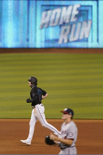 Miami Marlins' Brian Anderson, top, rounds second base after hitting a home run that also scored Garrett Cooper and Jesus Aguilar as Washington Nationals relief pitcher James Bourque, foreground, looks on during the fifth inning of the second game of a baseball doubleheader, Friday, Sept. 18, 2020, in Miami. (AP Photo/Wilfredo Lee)