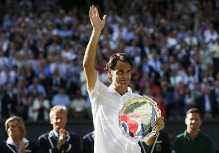 Roger Federer of Switzerland waves while holding the runner-up's trophy after being defeated by Novak Djokovic of Serbia in their men's singles finals tennis match on Centre Court at the Wimbledon Tennis Championships in London July 6, 2014. REUTERS/Stefan Wermuth