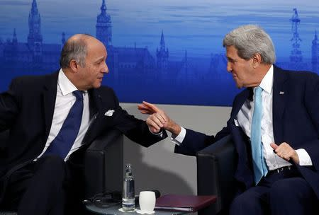 French Foreign Minister Laurent Fabius and U.S. Secretary of State John Kerry (R) discuss during the chairman's debate at the 51st Munich Security Conference at the 'Bayerischer Hof' hotel in Munich February 8, 2015. REUTERS/Michael Dalder