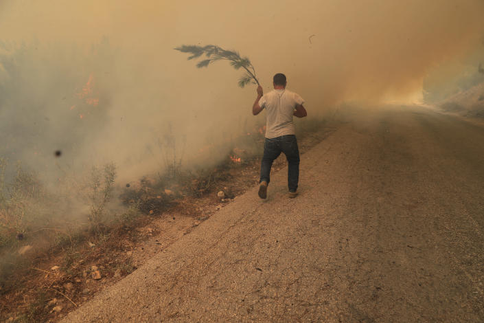 A man runs to extinguish a forest fire, at Qobayat village, in the northern Akkar province, Lebanon, Thursday, July 29, 2021. Lebanese firefighters are struggling for the second day to contain wildfires in the country's north that have spread across the border into Syria, civil defense officials in both countries said Thursday. (AP Photo/Hussein Malla)