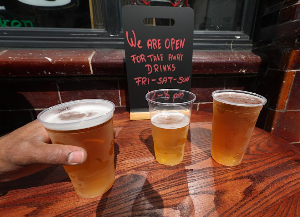 Takeaway pints of beer outside Charrington's Noted Ales And Stout pub in London, as further coronavirus lockdown restrictions are lifted in England.