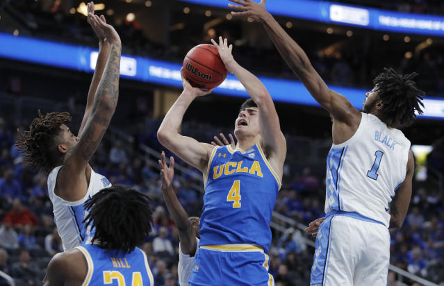UCLA's Jaime Jaquez Jr. (4) attempts a shot around North Carolina's Armando Bacot, left, and North Carolina's Leaky Black (1) during the second half of an NCAA college basketball game, Saturday, Dec. 21, 2019, in Las Vegas. (AP Photo/John Locher)