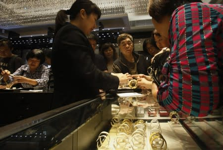Sales attendant shows gold bracelet to customers leaning over a half-empty display case at a jewellery store in Hong Kong