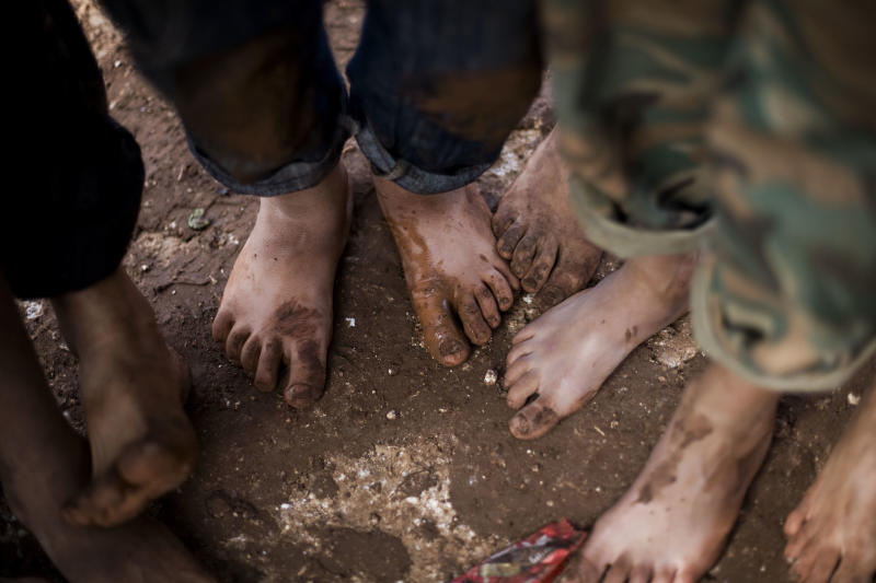 FILE - In this file photo taken Friday, Oct. 26, 2012, displaced Syrian children gather barefoot in a refugee camp near Atma, Idlib province, Syria. Children in Syria have been tortured, maimed and sexually abused by President Bashar Assad's forces and recruited for combat by the rebels fighting to topple him, according to a new United Nations report, posted on the U.N. website late Tuesday, Feb. 4, 2014. (AP Photo/Manu Brabo, File)