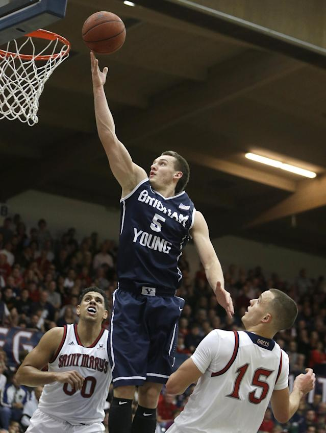 BYU's Kyle Collinsworth (5) lays up a shot between Saint Mary's Brad Waldow, left, and Beau Levesque (15) in the first half of an NCAA college basketball game on Saturday, Feb. 15, 2014, in Moraga, Calif. (AP Photo/Ben Margot)