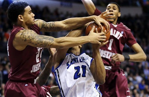 Saint Louis forward Dwayne Evans (21) heads to the basket as Saint Joseph center C.J. Aiken, right, watches and guard Chris Wilson, left, ties the ball up for a jump ball during the first half of an NCAA college basketball game, Wednesday, Feb. 27, 2013, in St. Louis. (AP Photo/Jeff Roberson)