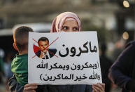 An Arab Israeli Muslim demonstrator, holding a child and clad in mask due to the COVID-19 coronavirus pandemic, holds up a sign during a rally protesting against the comments of French President Emmanuel Macron over Prophet Mohammed cartoons, in the Arab town of Umm-Al Fahem in Northen Israel on October 25, 2020. (Photo by Ahmad GHARABLI / AFP) (Photo by AHMAD GHARABLI/AFP via Getty Images)