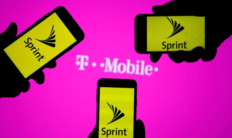 FILE PHOTO: A smartphones with Sprint logo are seen in front of a screen projection of T-mobile logo, in this picture illustration