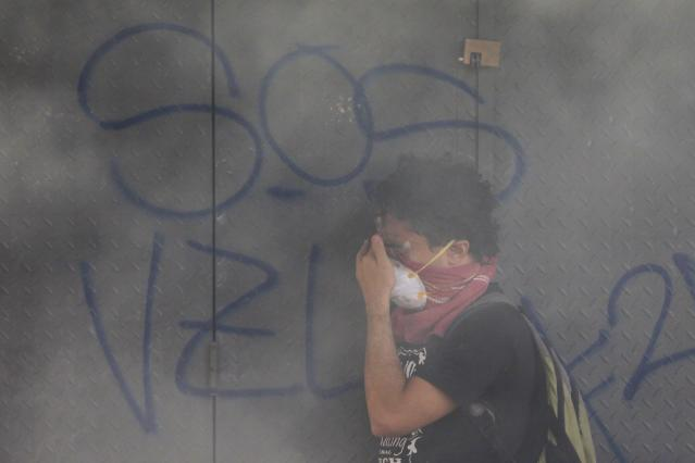 An anti-government protester reacts to teargas during a protest in Caracas March 9, 2014. Latin American foreign ministers will meet next week to discuss the unrest in Venezuela that has left at least 20 dead and convulsed the South American OPEC nation, diplomatic sources said on Friday. REUTERS/Tomas Bravo (VENEZUELA - Tags: POLITICS CIVIL UNREST)