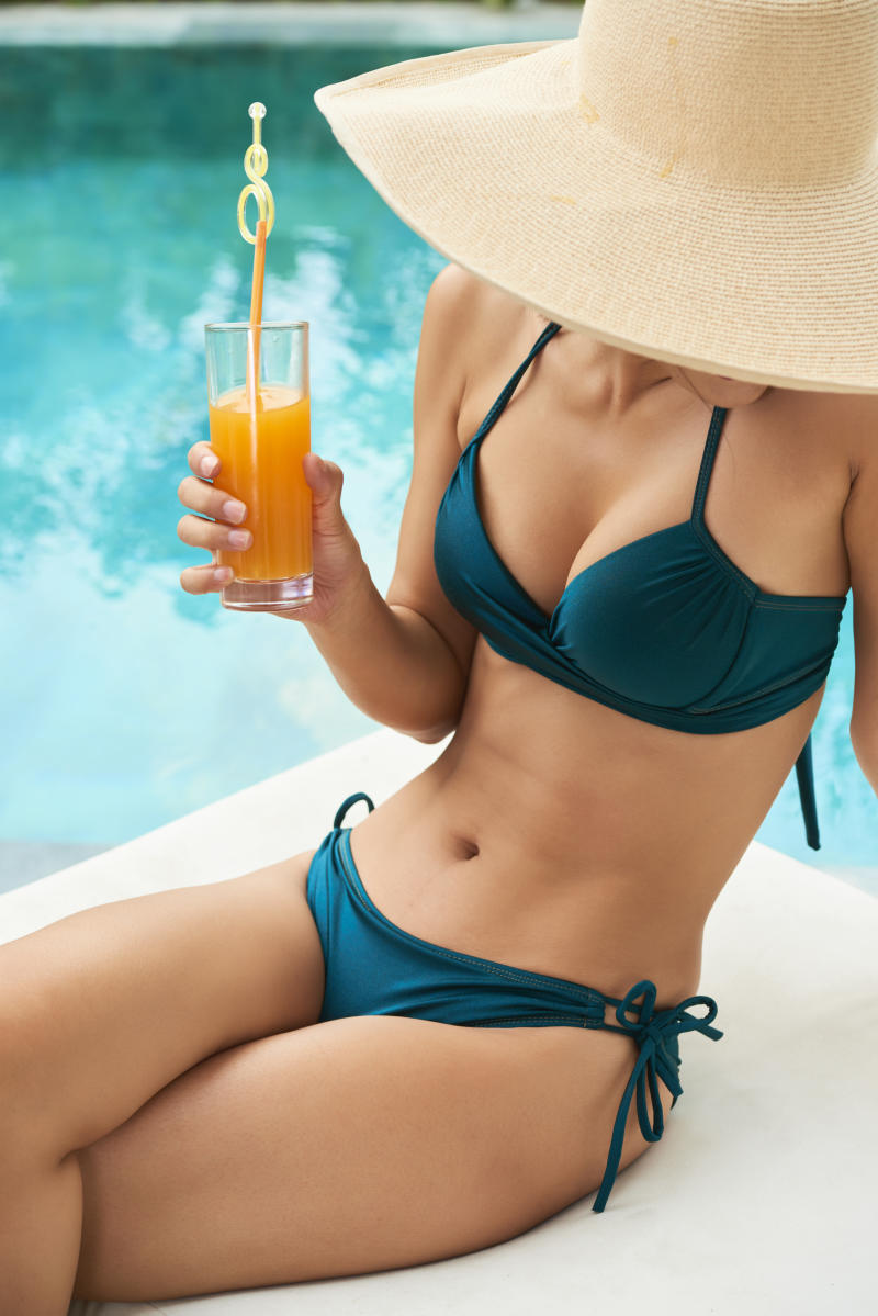 Young woman with beautiful body wearing bikini and hat drinking cocktail and sunbathing at poolside