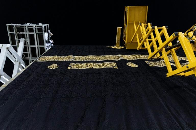 Labourers carry out the annual changing of the kiswa, the protective cover of black silk embroidered with Koranic verses in gold thread, that adorns the Kaaba, the stone cube which pilgrims walk round at the heart of Mecca's Grand Mosque (AFP Photo/Raeid AL-LEHYANI)