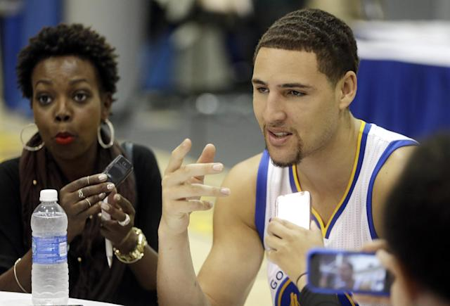Golden State Warriors' Klay Thompson, right, answers questions from reporters during NBA basketball media day, Monday, Sept. 29, 2014, in Oakland, Calif. (AP Photo/Ben Margot)