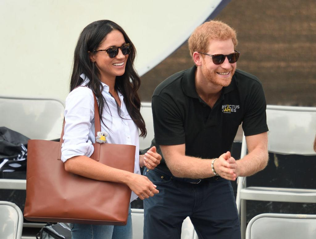 <p>Markle complemented the shirt with a pair of ripped jeans and $600 tan leather shoes by Sarah Flint. She finished the look with a $200 cognac leather tote by Everlane and $200 Finlay & Co sunglasses. <em>(Photo: Getty)</em> </p>