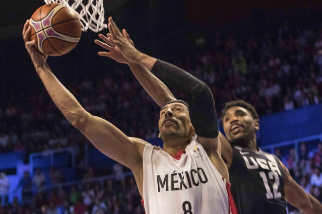 Mexico's Gustavo Ayon, left, goes for the basket to score, under the pressure from U.S. player Kevin Jones during the third quarter of a regular season FIBA basketball World Cup qualifier in Mexico City, Thursday, June 28, 2018. (AP Photo/Christian Palma)