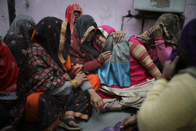 Family members of Rahul Solanki, who was killed during clashes between Hindu mobs and Muslims protesting a contentious new citizenship law, weep outside a mortuary in New Delhi, India, Wednesday, Feb. 26, 2020. At least 20 people were killed in three days of clashes in New Delhi, with the death toll expected to rise as hospitals were overflowed with dozens of injured people, authorities said Wednesday. The clashes between Hindu mobs and Muslims protesting a contentious new citizenship law that fast-tracks naturalization for foreign-born religious minorities of all major faiths in South Asia except Islam escalated Tuesday. (AP Photo/Altaf Qadri)
