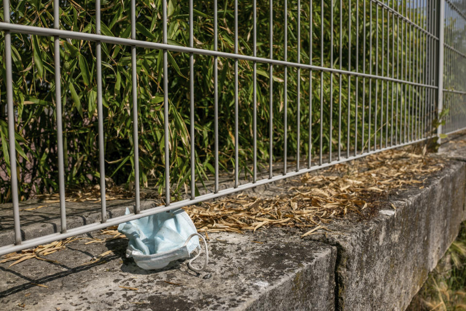 An abandoned mask is pictured in a garden Wednesday, June 16, 2021 in Paris. France on Wednesday eased several COVID-19 restrictions, with authorities saying it's no longer always mandatory to wear masks outdoors, and halting an 8-month nightly coronavirus curfew this weekend. (AP Photo/Benjamin Girette)