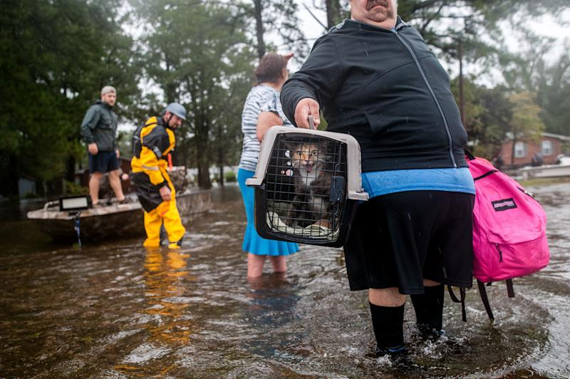 Orlando Collazo holds a pet carrier with his family's cats, Princess and Gizmo, after they were pulled from their flooded home by members of the Cajun Navy in Lumberton, North Carolina, on Sunday. (Joseph Rushmore for HuffPost)