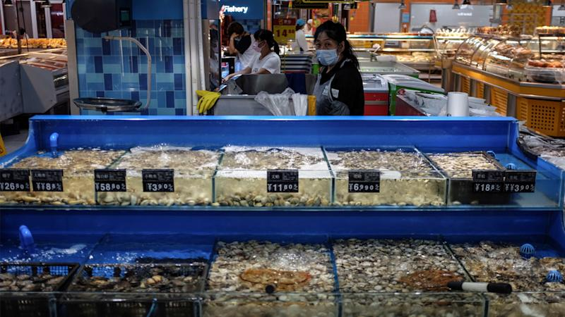 A salesperson wearing a face mask stands at a seafood stall in a supermarket following the confirmation of new SARS-CoV-2 cases in Beijing. Source: AAP
